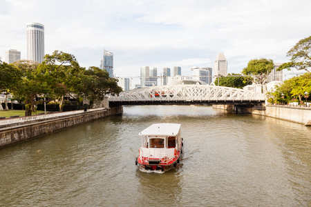 A boat ply the Singapore River on Boat Quay toward Anderson Bridge, with the citys skyline in the background.