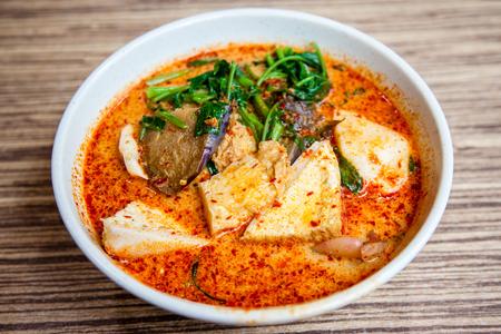 Uma tigela de Cingapura Laksa Yong Tau Foo, um popular prato local servido em pasta de molho picante de caril com molho de leite de coco; tofu e berinjela recheados com pasta de peixe; legumes; cortador e fishball sobre macarrão grosso por baixo. Isso é um favor Foto de archivo - 87249230