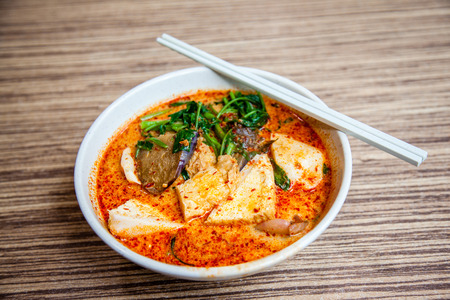 A bowl of Singapore Laksa Yong Tau Foo, a popular local dish served in spicy curry shrimp paste gravy soup base with coconut milk; tofu and eggplant filled with fish paste; vegetables; cutterfish and fishball over thick noodles underneath. This is a favor