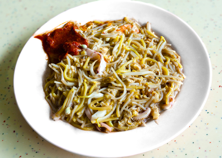 Singapore Hokkien mee is a popular local cuisine in Malaysia and Singapore that has its origins in the Chinas Fujian province. The dish consists of egg noodles and rice noodles stir-fried with prawns, calamari, eggs, pork and served with sambal chilli an 版權商用圖片