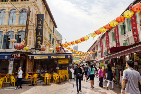 SINGAPORE - SEPTEMBER 11, 2017: Shoppers visiting Chinatown for bargain souvenirs and authentic local food. The old Victorian-style shophouses are a trademark of this popular area. Singapore's Chinatown was originally designated for Chinese settlement by  Sajtókép
