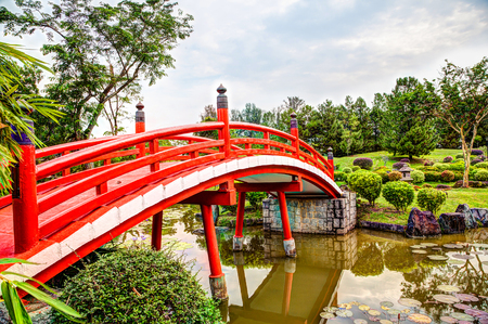 Red wooden bridge over tranquil pond at Japanese Garden, a free public park within Jurong Lake Gardens in Singapore. The gardens are popular among exercise enthusiasts, bird watchers and nature lovers. Stock Photo - 87708867
