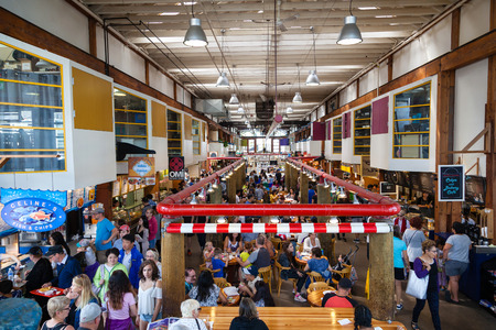 VANCOUVER, CANADA - AUG. 16, 2017: Visitors eating at the Granville Island Public Market. Its home to over 100 vendors offering fresh seafood, meats, and specialty foods. Granville Island is located across False Creek from downtown Vancouver.