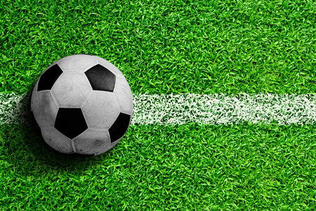 Soccer ball on field with white line marking ready for action. Line represents kickoff or sideline for throw in. Copy space. Stock Photo