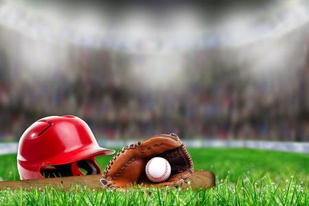 야구 헬멧, 박쥐, 장갑 및 필드 잔디에 공 및 복사 공간이 밝은 조명 된 경기장 배경에 필드의 고 의적으로 얕은 깊이의 낮은 각도보기.