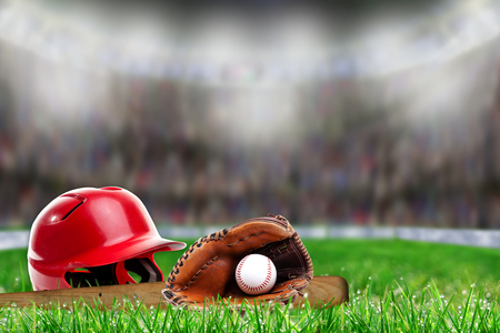 Low angle view of baseball helmet, bat, glove and ball on field grass and deliberate shallow depth of field on brightly lit stadium background with copy space.