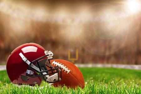 축구 헬멧 및 필드 잔디에 공을의 낮은 각도보기 및 복사 공간이 밝은 조명 된 경기장 배경에 필드의 고 의적으로 얕은 깊이.