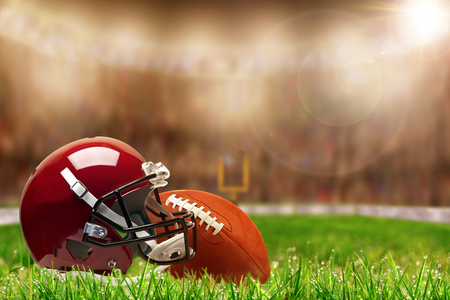 Low angle view of football helmet and ball on field grass and deliberate shallow depth of field on brightly lit stadium background with copy space. Stock Photo