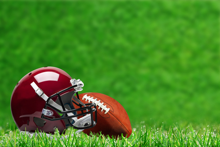 Low angle view of football helmet and ball on field grass and deliberate shallow depth of field on background with copy space.