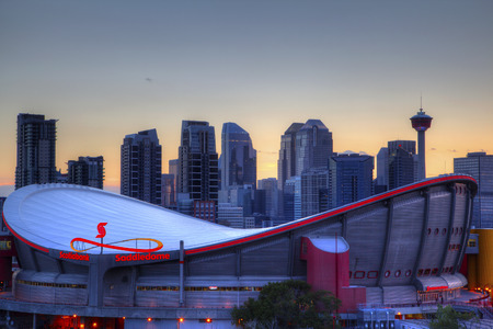 CALGARY, CANADA - MAY 23, 2015: Sunset over Calgarys skyline with the Scotiabank Saddledome in the foreground. The dome with its unique saddle shape is home to the Calgary Flames NHL club, and is one of the oldest professional hockey arenas in North Amer Editorial