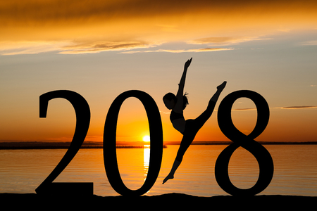 2018 New Year silhouette of a girl dancing or exercising at the beach during golden sunrise or sunset with copy space.