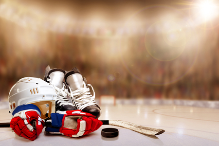 Low angle view of hockey helmet, skates; gloves; stick and puck on ice with deliberate shallow depth of field on brightly lit stadium background and copy space. Stock Photo