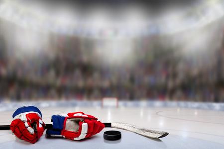 Lage hoekmening van hockeyhandschoenen; stick en puck op ijs met opzettelijke ondiepe scherptediepte op fel verlichte stadion achtergrond en kopie ruimte.