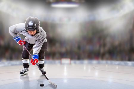 Lage hoekmening van hockey speler behandeling puck op ijs met sportarena vol fans in de stands en kopie ruimte. Ondiepe scherptediepte op achtergrond. Stockfoto