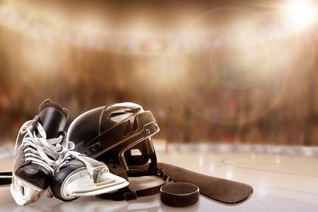 Lage hoekmening van hockeyhelm, vleten; stick en puck op ijs met opzettelijke ondiepe scherptediepte op fel verlichte stadion achtergrond en kopie ruimte.