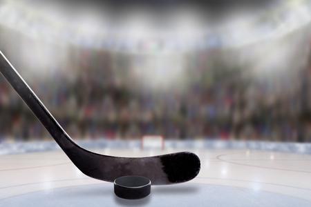 Lage hoekmening van hockeystick en puck op ijs met opzettelijke ondiepe diepte van gebied op helder aangestoken stadionachtergrond en exemplaarruimte.