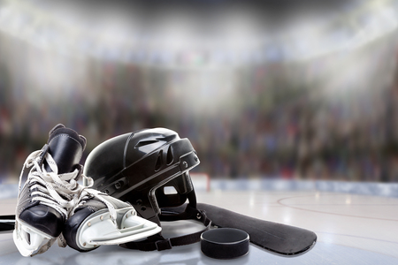Low angle view of hockey helmet, skates; stick and puck on ice with deliberate shallow depth of field on brightly lit stadium background and copy space.