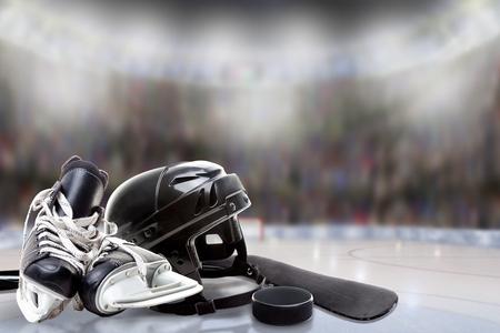 하 키 헬멧, 스케이트의 낮은 각도보기; 막대기와 밝은 조명 된 경기장 배경 및 복사 공간에 필드의 고의적으로 얕은 깊이와 얼음에 퍽.