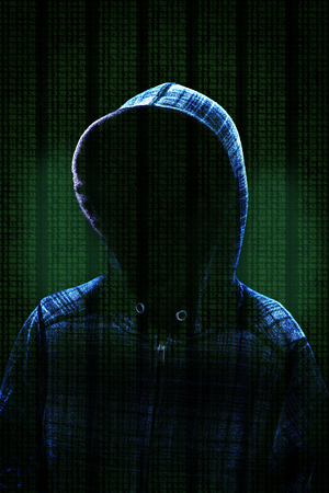 Unknown computer hacker with hood against background data and dramatic lighting with copy space. Concept of cybercrime.