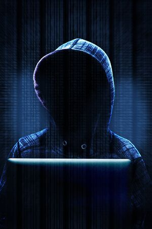 Unknown computer hacker with hood working on computer laptop in committing cyber crime on the Internet. Background data and dramatic lighting with copy space. Stock Photo