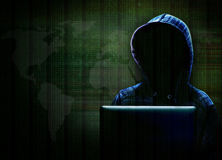 Unknown computer hacker with hood committing cyber crime with background data and world map in dramatic lighting with copy space. Stock Photo