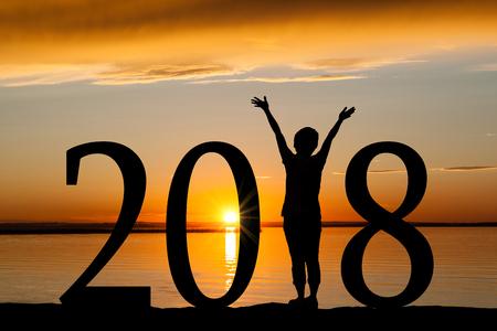 Silhouette de nouvel an 2018 d'une fille avec les mains levées à la plage pendant le lever ou le coucher du soleil d'or avec l'espace de copie. Concept de joie, de louange, de culte, de connexion avec la nature. Banque d'images - 90073232