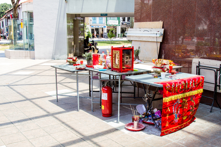 SINGAPORE - SEPTEMBER 7, 2017: A makeshift Chinese altar was erected at a street corner to make offerings to spirits during the Hungry Ghost Festival on the seventh month on the lunar calendar. This time every year, Buddhists and Taoists believe the gates