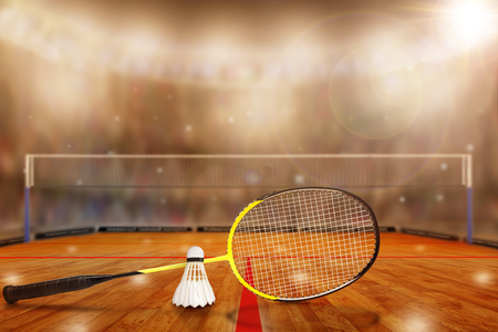 Low angle view of badminton arena with sports fans in the stands and copy space. Focus on foreground racket and shuttlecock with deliberate shallow depth of field on background.