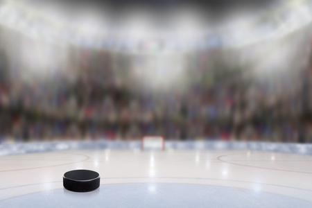 Lage hoekmening van ijshockeypuck op ijs met opzettelijke ondiepe diepte van gebied op helder aangestoken stadionachtergrond en exemplaarruimte.