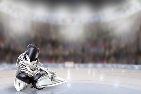 Lage hoekmening van hockeyvleten op ijs met opzettelijke ondiepe diepte van gebied op helder verlichte stadionachtergrond en exemplaarruimte.