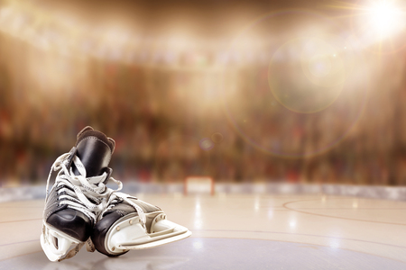 Low angle view of hockey skates on ice with deliberate shallow depth of field on brightly lit stadium background and copy space.