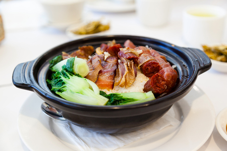 Chinese steamed pork and liver sausages with vegetables and rice in claypot is a popular dish in Cantonese dim sum restaurants in Hong Kong and Southern China. Reklamní fotografie - 94033421