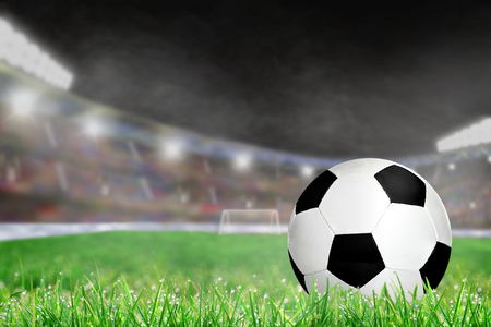 Soccer ball on field grass in brightly lit outdoor stadium with focus on foreground and deliberate shallow depth of field on background. Copy space.