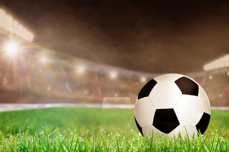 Soccer ball on field grass in brightly lit outdoor stadium with focus on foreground and shallow depth of field on background. Deliberate lens flare and copy space. Stock Photo