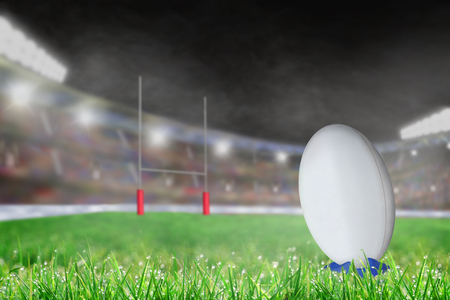 White rugby ball on a kicking tee on the grass ready for conversion or penalty kick toward goal post. Deliberate shallow depth of field on brightly lit stadium background with copy space. 스톡 콘텐츠