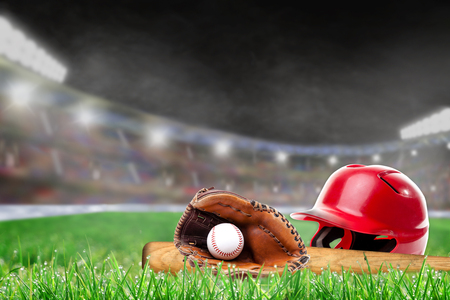 Baseball helmet, bat, glove and ball on grass in brightly lit outdoor stadium with focus on foreground and shallow depth of field on background. Deliberate lens flare and copy space.