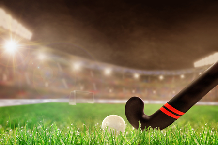 Field hockey stick and ball on grass in brightly lit outdoor stadium with focus on foreground and shallow depth of field on background. Deliberate lens flare and copy space. 스톡 콘텐츠