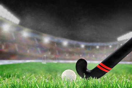 Bâton de hockey sur gazon et balle sur l'herbe dans un stade extérieur bien éclairé avec un accent sur le premier plan et une faible profondeur de champ en arrière-plan. Éblouissement délibéré et espace de copie.