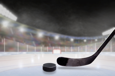 Ice hockey stick and puck in brightly lit outdoor stadium with focus on foreground and shallow depth of field on background. Deliberate lens flare and copy space. Banque d'images
