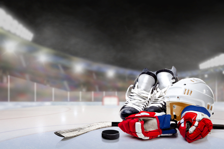 Ice hockey helmet, skates, gloves, stick and puck in brightly lit outdoor stadium with focus on foreground and shallow depth of field on background. Deliberate lens flare and copy space.