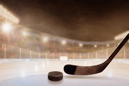 Ice hockey stick and puck in brightly lit outdoor stadium with focus on foreground and shallow depth of field on background. Deliberate lens flare and copy space. Stock Photo
