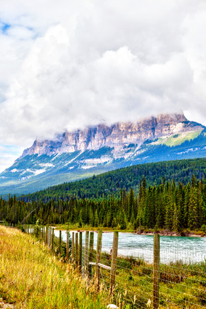 Clouds descend on top of Castle Mountain in Banff National Park, Canada, at the eastern ranges of the Bow Valley with Bow River flowing. Vertical orientation.