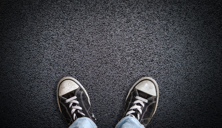 A teenager in jeans and canvas shoes standing on asphalt road with copy space. Concept of standing at the crossroads to contemplate a decision.