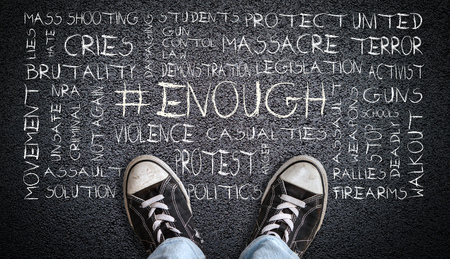 A teenager in jeans and canvas shoes standing on asphalt road with # ENOUGH word cloud. Concept of social movement to protest gun violence and mass school shootings in the United States.