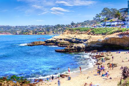 サンディエゴの人気の海辺の町ラホヤコーブでは、ビーチに群衆、海のカヌー、岩の上で休んでいるアシカのグループがあります。