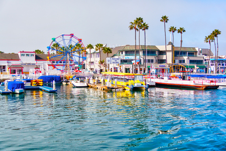 NEWPORT BEACH, CA, USA - MAR 29, 2018: Popular pier at Balboa peninsula in Southern California with ferris wheel, tourist shops, restaurants and boats doting the harbor ferry terminal.