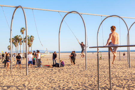 SANTA MONICA, USA - MAR 26, 2018: A crowd working out on the traveling rings and parallel bars at Santa Monica beach in California renowned as the birthplace of the U.S. physical fitness boom.