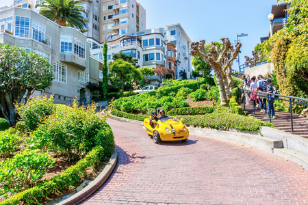SAN FRANCISCO - APR 2, 2018: Tourists drive down crooked Lombard Street on a GoCar, a scooter created with the purpose of being rented to tourists as a different way to explore a city. It is the world