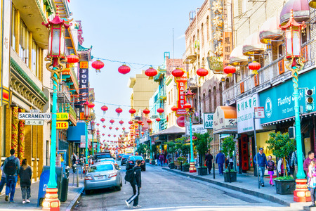 SAN FRANCISCO - APR 2, 2018: Red lanterns hang along busy Grant Avenue in the heart of San Francisco Chinatown. Teeming with Chinese restaurants and shops, it is one of the oldest and largest Chinatowns in North America. 新聞圖片