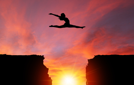 Silhouette of girl dancer in a split leap over dangerous cliffs with dramatic sunset or sunrise background and copy space. Concept of faith, conquering adversity, taking risk; challenge, courage, determination or achievement.